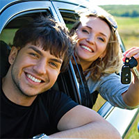 Couple leaning out of car window holding keys.